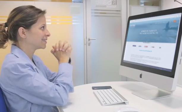 Chica feliz frente a un monitor de ordenador