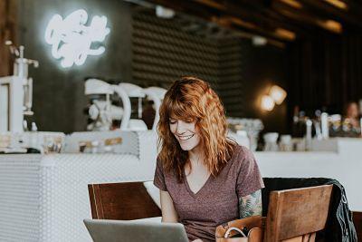 Chica feliz delante de un ordenador portátil